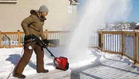 Woman using an electric snowblower